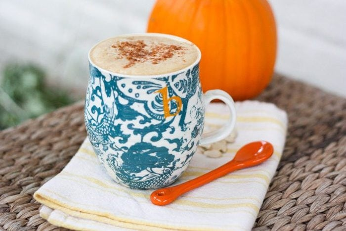 Pumpkin spice latte in a blue mug on a kitchen towel. Pumpkin in the background.