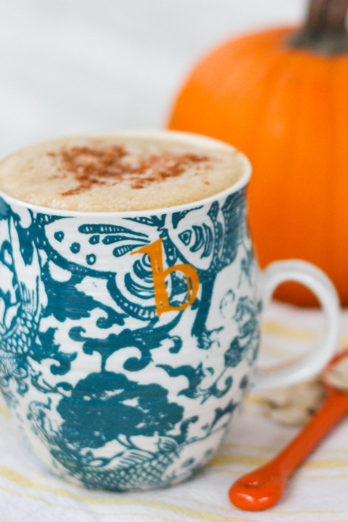Homemade Pumpkin Spice Latte in a blue mug sitting on a kitchen towel.