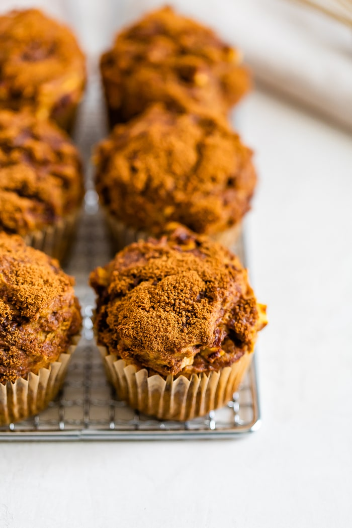 Apple muffins topped with cinnamon sugar on a cooling rack.