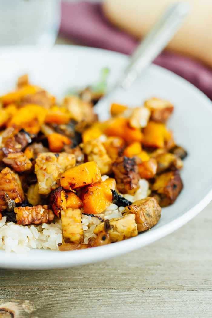 Tempeh and butternut squash bake with tempeh, squash and mushrooms, topped on a plate of rice.