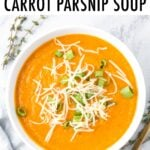 Bowl of carrot parsnip soup topped with green onion and cheese.