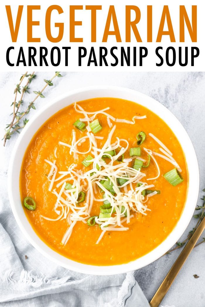 Bowl of carrot parsnip soup garnished with green onion and cheese.