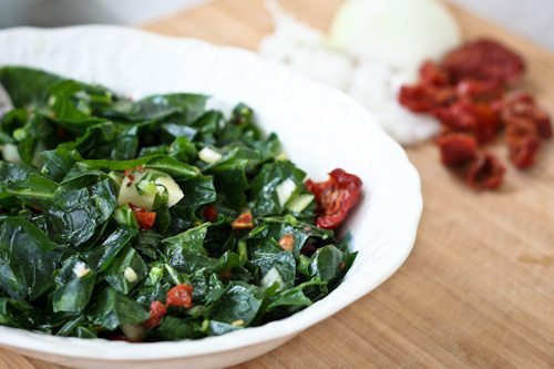 Raw Collard Green Salad in a white serving dish.