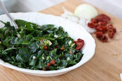 Raw Collard Greens in a white serving bowl on a wood countertop.