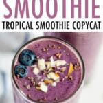 A purple health nut smoothie topped with blueberries, chopped almonds, and cacao nibs.