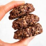 A hand holding a stack of three peanut butter chocolate no bake cookies.