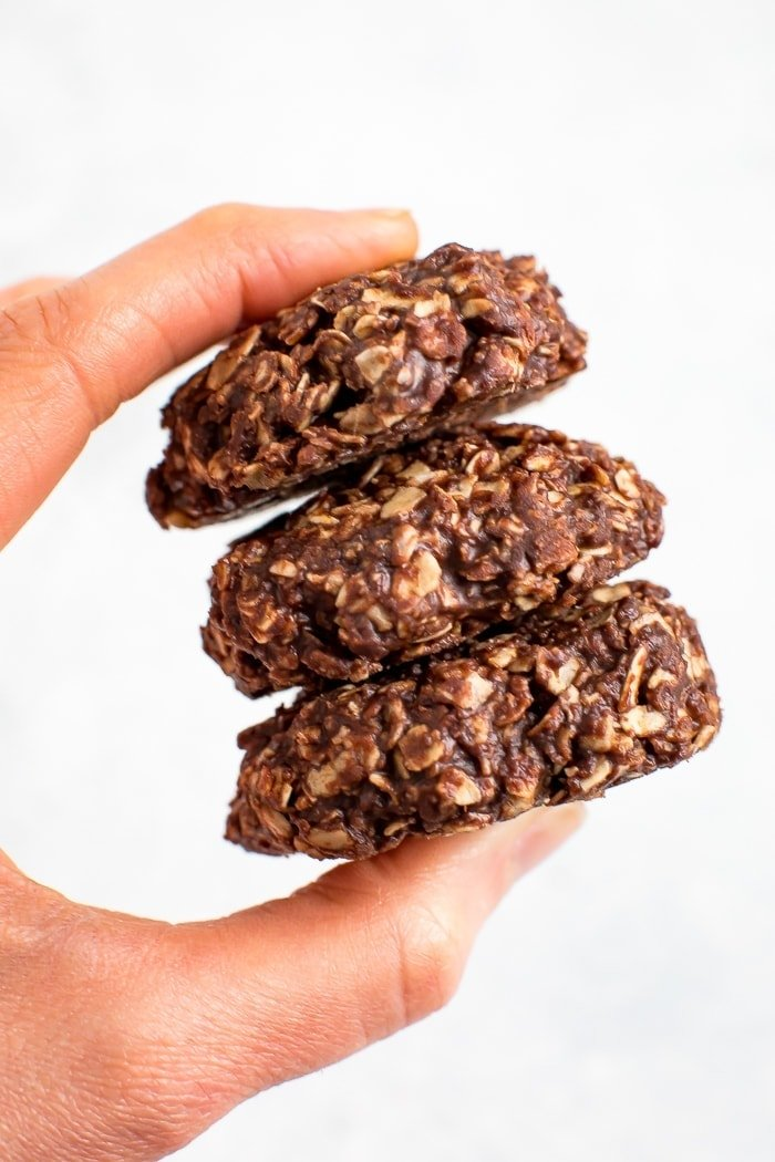 Hand holding a stack of three peanut butter chocolate healthy no bake cookies.