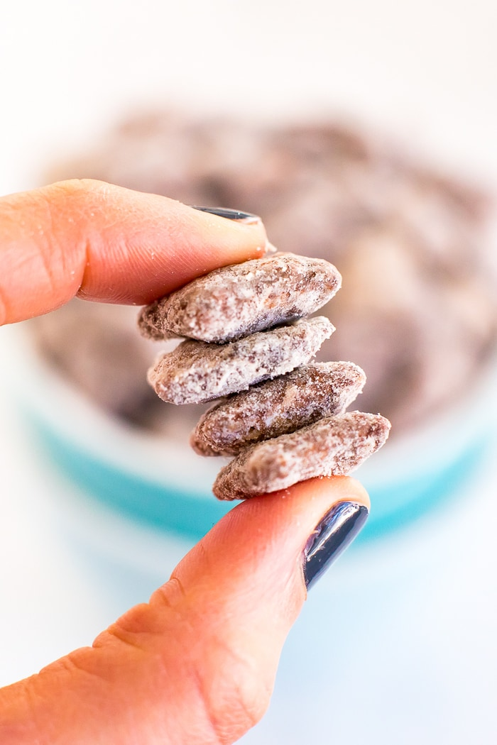 A hand holding four pieces of protein muddy buddy mix.