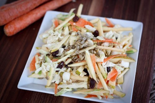 Cabbage, Carrot, and Apple Salad served on a white plate on wood cutting board.