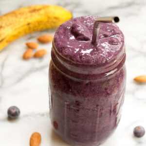 Blueberry Almond Smoothie in a clear mason jar with stainless steel straw on white marble countertop.