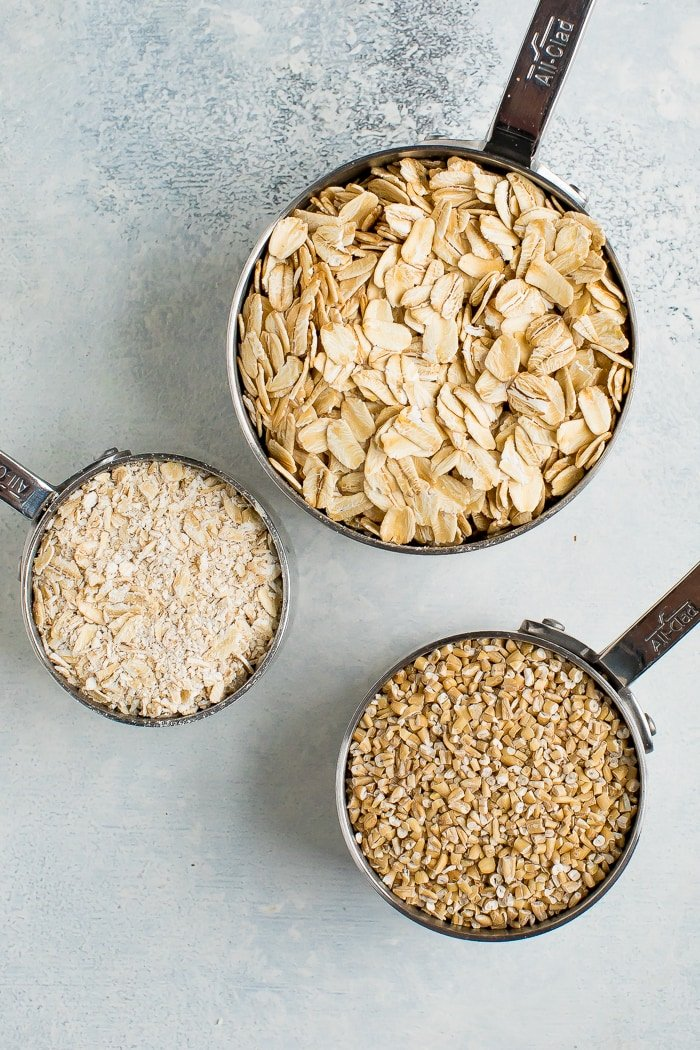 3 measuring cups with rolled oats, steel cut oats and quick oats.