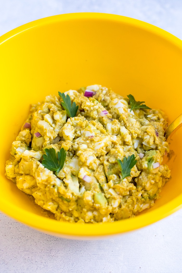Curried avocado egg salad in a yellow bowl with parsley leaves on top.