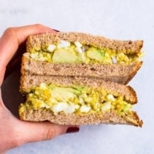 A hand holding curried avocado egg salad in a sandwich that is cut in half..