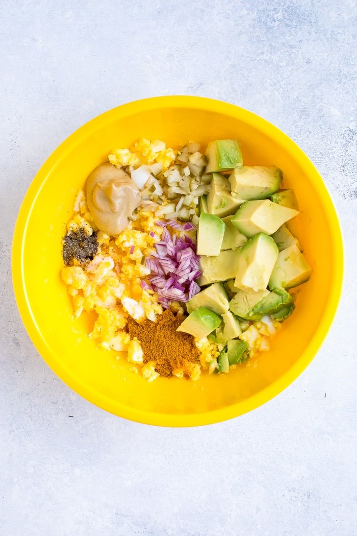 A yellow bowl with all the ingredients to make curried avocado egg salad.