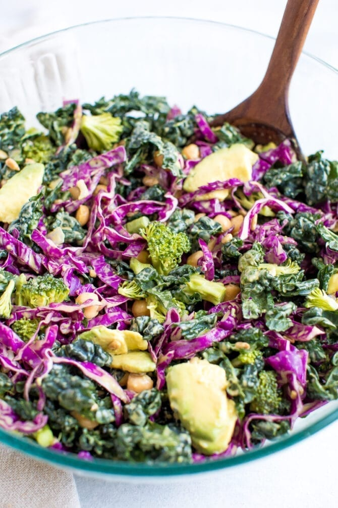 Salad with kale, cabbage, avocado, broccoli, chickpeas, and a nutritional yeast goddess dressing in a bowl.