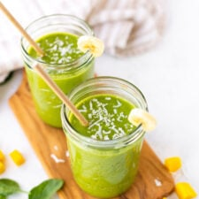Two Ball mason jars filled with a green smoothie sitting on a wooden cutting board with spinach, mango and coconut shreds scattered around.