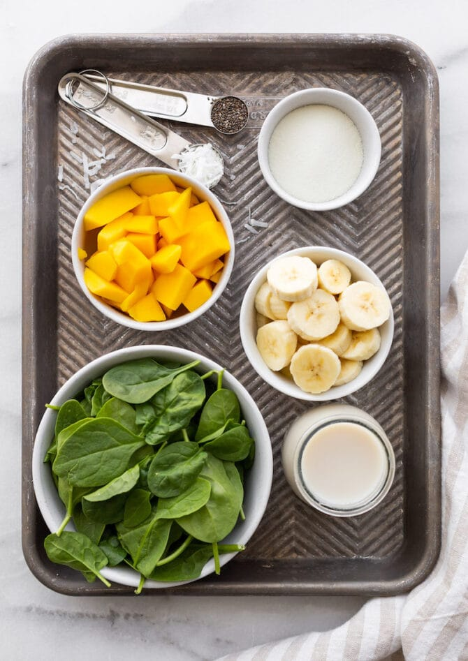 Ingredients for tropical green smoothie laid out on a baking tray: baby spinach, milk, banana slices, mango chunks, protein powder, chia seeds and shredded coconut.