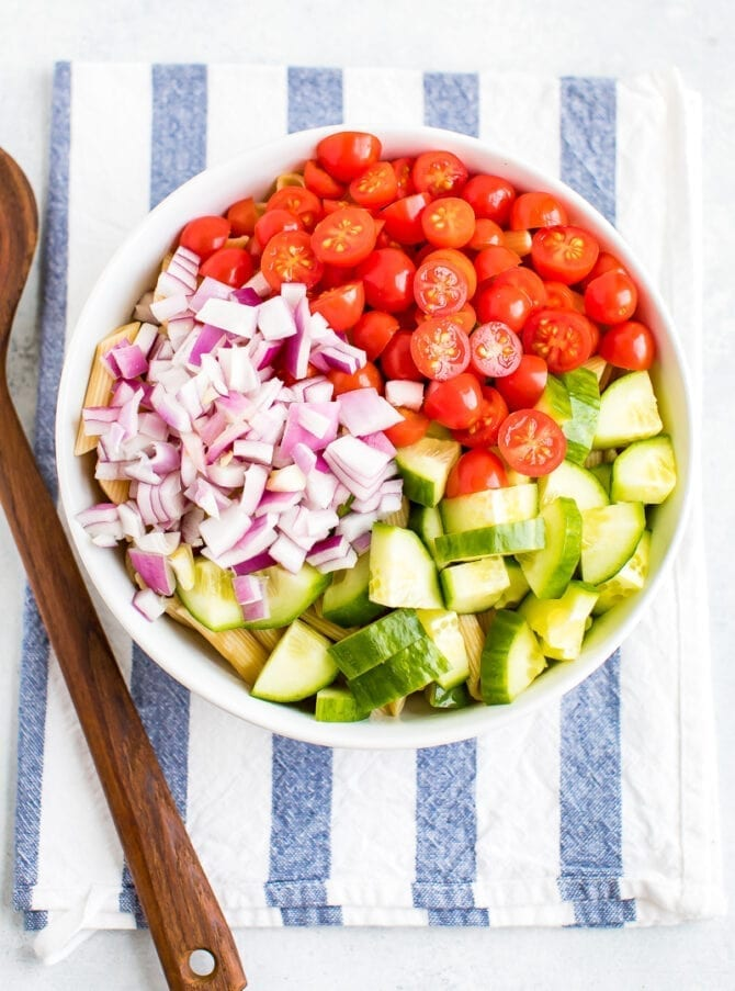 Bowl with ingredients for healthy pasta salad before mixing. In the bowl, on top fo penne are sections of chopped red onion, cherry tomatoes and chopped cucumber. Wood spoon and striped dish towel are by the bowl.