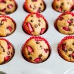 Strawberry chocolate chip protein muffins in red cupcake liners in a muffin tin. Muffins are topped with chopped strawberries and mini chocolate chips.