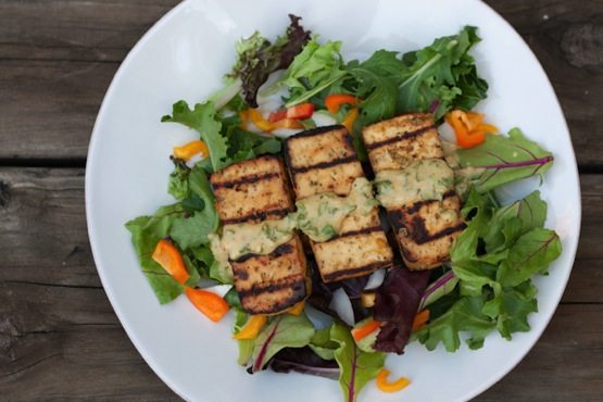 Overhead photo of a plate with lemon basil tofu on a bed of mixed greens.
