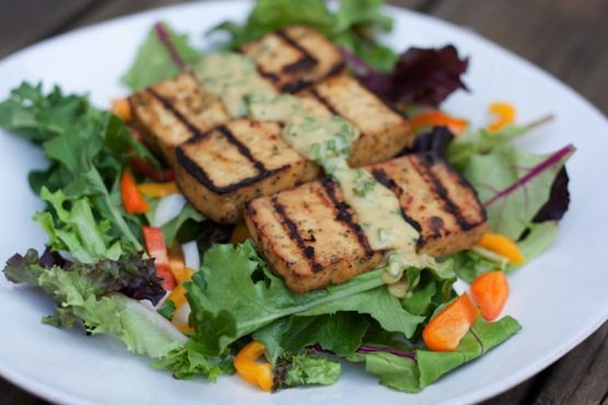 A plate with basil lemon tofu on a bed of mixed greens.