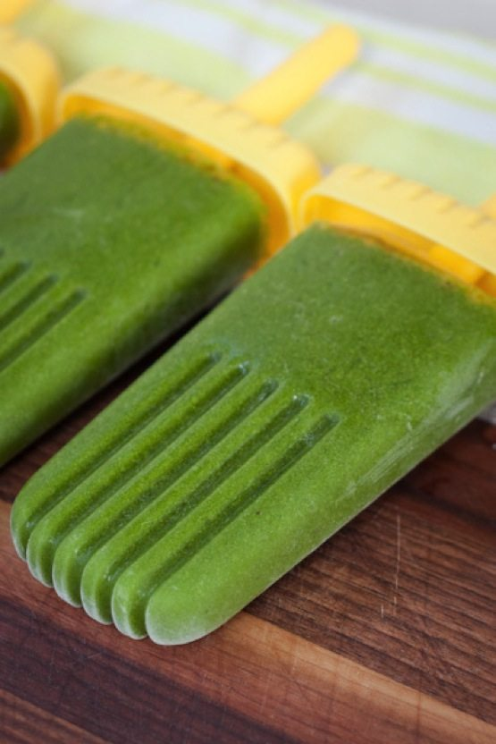 Green Smoothie Protein Popsicles on wood cutting board.