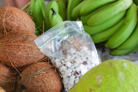 Bag of coconut meat next to fresh coconuts and green bananas.