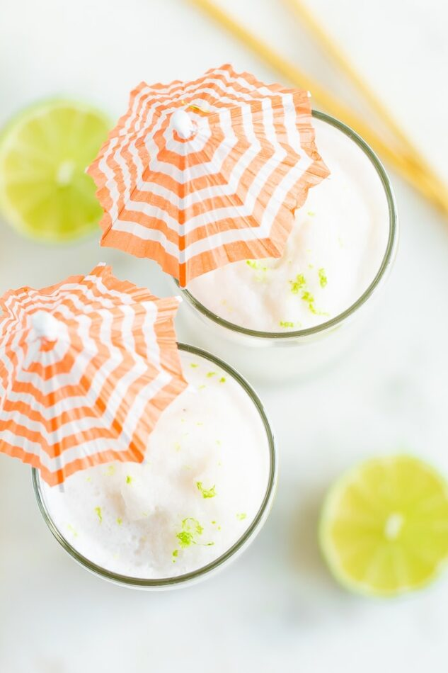 Overhead shot with two skinny coconut daiquiri cocktails in tall glasses with orange and white striped cocktail umbrellas.