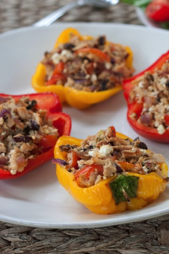 Four red and yellow tuna stuffed peppers on a white plate.