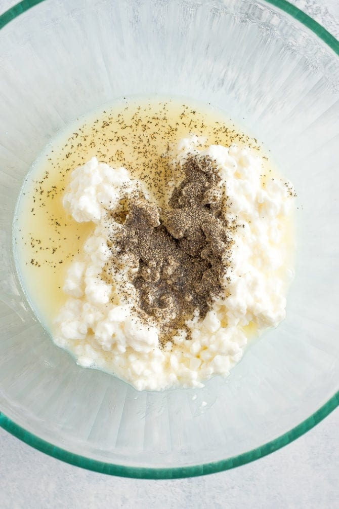 Cottage cheese and egg whites with spices in a bowl for the healthier ricotta filling.