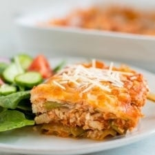 Slice of zucchini noodle tofu lasagna on a plate with salad.