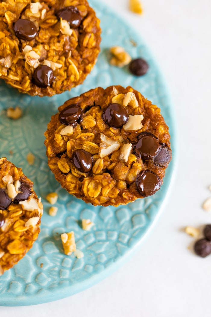 Three baked pumpkin oatmeal cups on a plate. Oatmeal cups are topped with walnuts and chocolate chips.