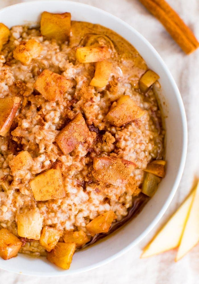Healthy apple cinnamon oatmeal in bowl topped with apple chunks and cinnamon .