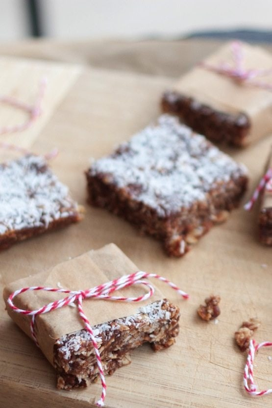 No bake chocolate coconut bars on a cutting board with one wrapped in parchment with red and white twine.