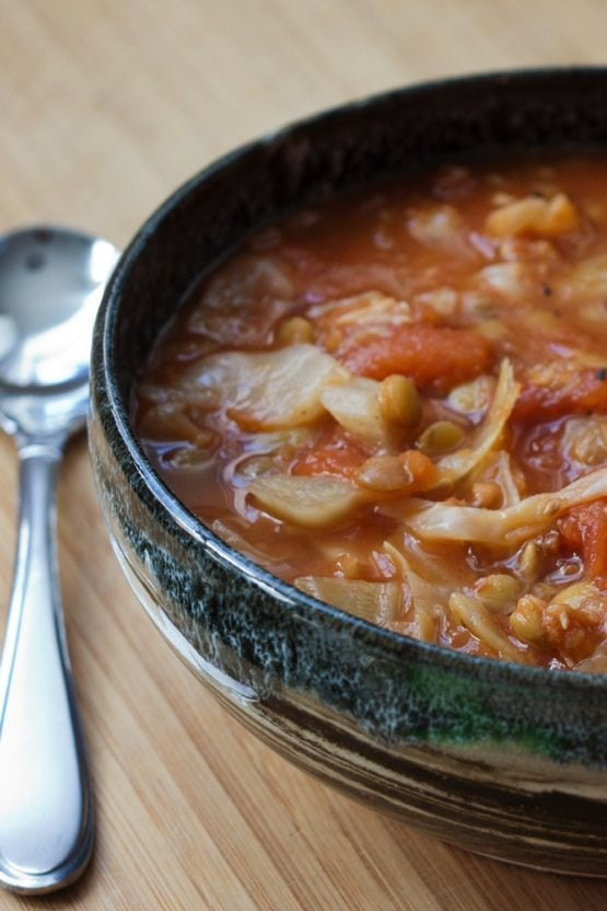 Health Boosting Cabbage Lentil Soup in a shallow bowl with a silver spoon on the side.
