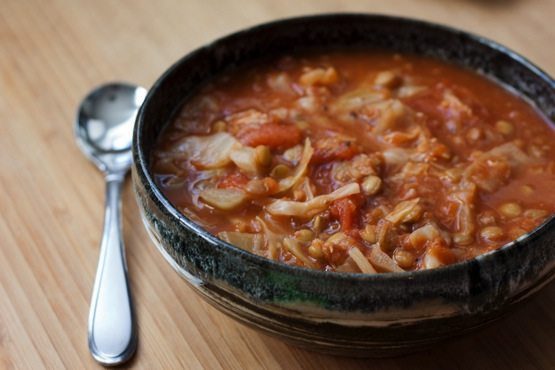 Health Boosting Cabbage Lentil Soup in a shallow bowl on a wood table with a silver spoon sitting next to the bowl.
