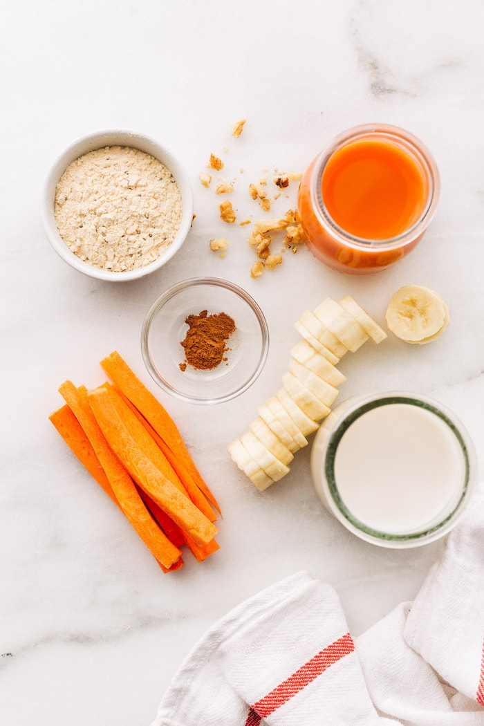 Ingredients to make carrot cake protein smoothie separated out on a table: carrot juice, protein powder, almond milk, cinnamon and sliced frozen banana.