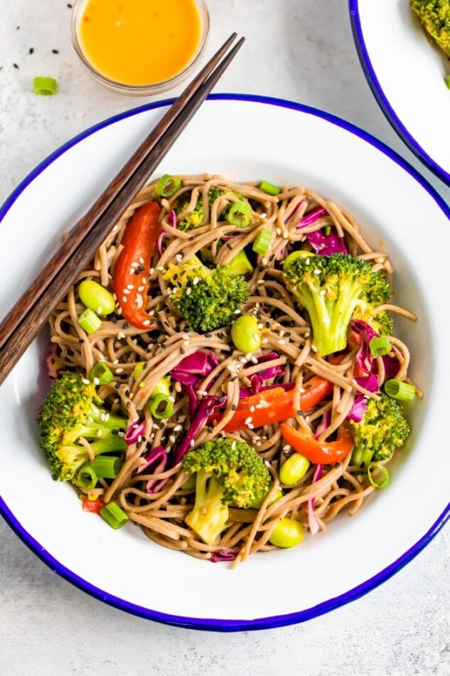 Bowl of soba noodle salad, with red pepper, broccoli, edamame, and purple cabbage, and topped with sesame seeds.