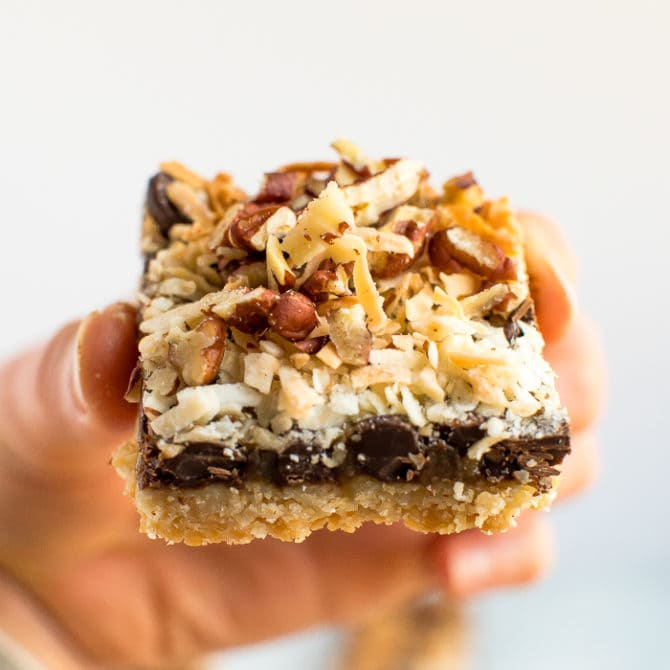 Hand holding a healthier, gluten free, grain free, vegan, magic cookie bar. An almond flour cookie crust topped with coconut caramel, coconut, pecans, and chocolate chips.