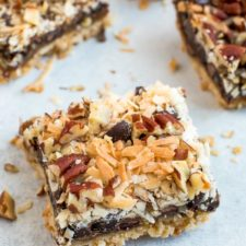 Healthier square magic cookie bars. An almond flour cookie crust topped with coconut caramel, coconut, pecans, and chocolate chips.
