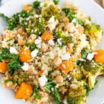 A white plate piled with roasted broccoli and quinoa salad. Salad also has kale, sweet potatoes, feta, and chickpeas. Checkered napkin below the plate.