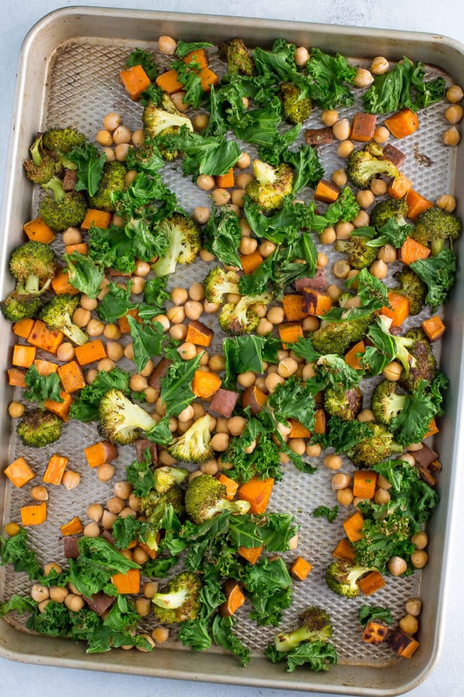 Roasted broccoli, kale, sweet potatoes and chickpeas on a baking sheet.