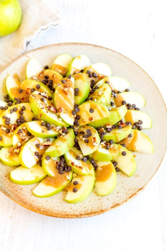 These healthy apple nachos are sure to satisfy even the strongest sugar craving; sliced apples piled high with date caramel, chocolate chips, and nuts. Vegan and Gluten Free.