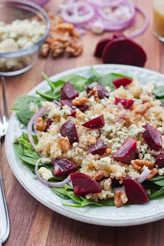 Spinach, Beet and Quinoa Power Salad served on a white plate in front of fresh salad ingredients.