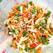 Glass bowl with wooden salad spoons tossing a salad made from kale, cabbage, chickpeas, carrots, onion, and peppers. Sprigs of cilantro are to the side on the table.