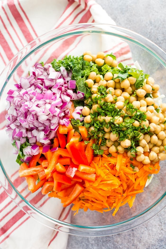Glass bowl filled with the ingredients for the pad thai salad sectioned out. There are chopped onion, chickpeas, cilantro, carrots, and red pepper on top of kale and cabbage. Bowl is on a kitchen towel.
