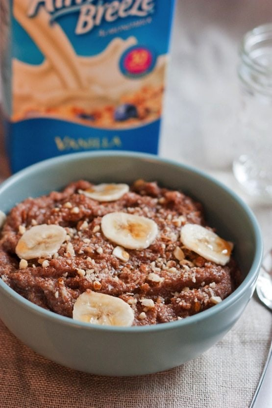 Banana Almond Teff Porridge in a light blue bowl. Almondmilk container in background.