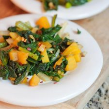A close up of golden beet greens on a white plate.