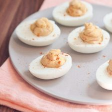 White plate with 5 hummus deviled eggs.