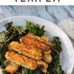 "Lemon garlic tempeh slices over a bed of cooked kale. Text above says ""Lemon Garlic Tempeh"""
